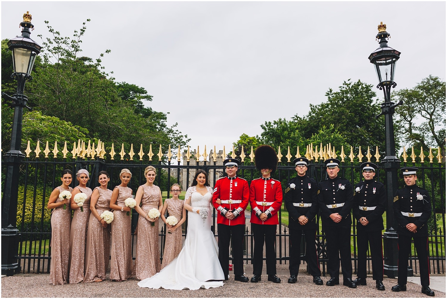 Windsor wedding. Bride and groom with bridal party in front of the gates at Windsor Castle