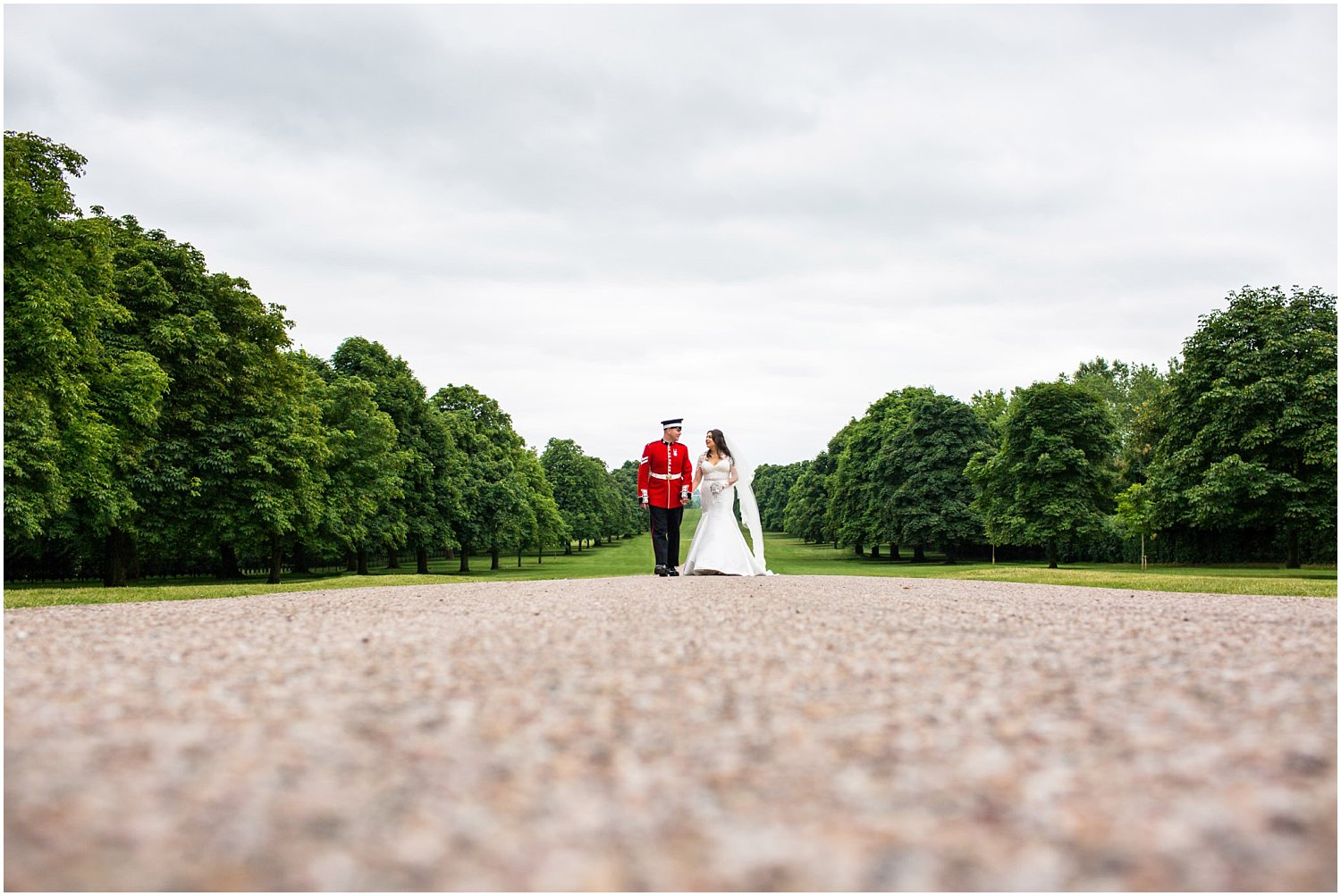 Windsor wedding. Bride and groom walking up the Long Walk