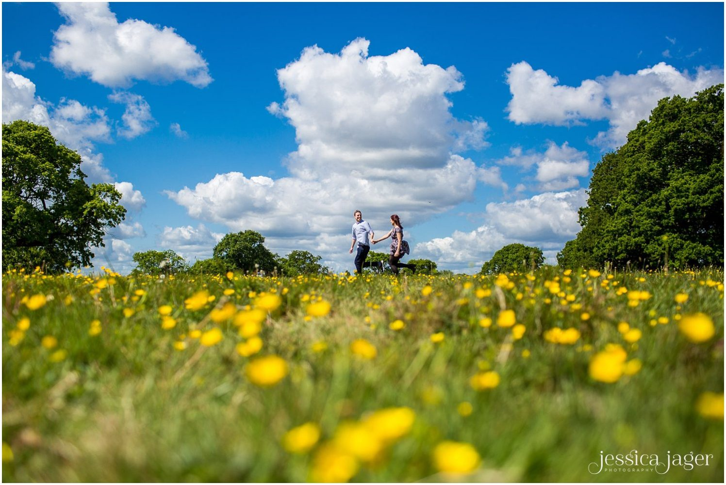 Couple holding hands and running across a meadow of buttercups