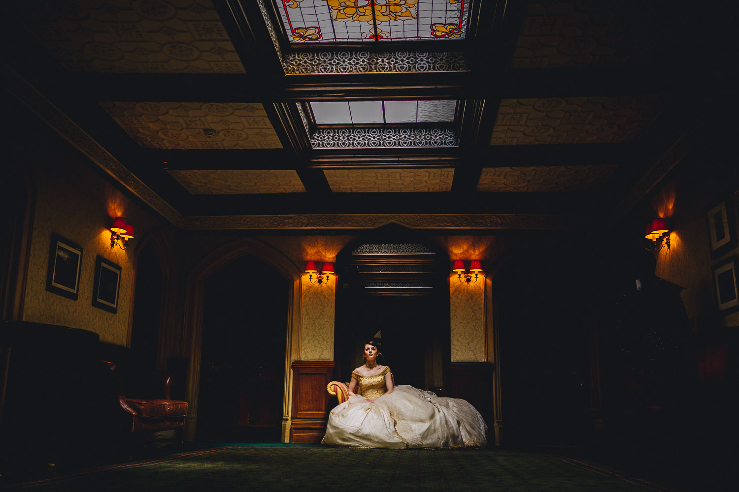 Bride sitting on a sofa with light falling on her from skylights at Oakley Court hotel Windsor