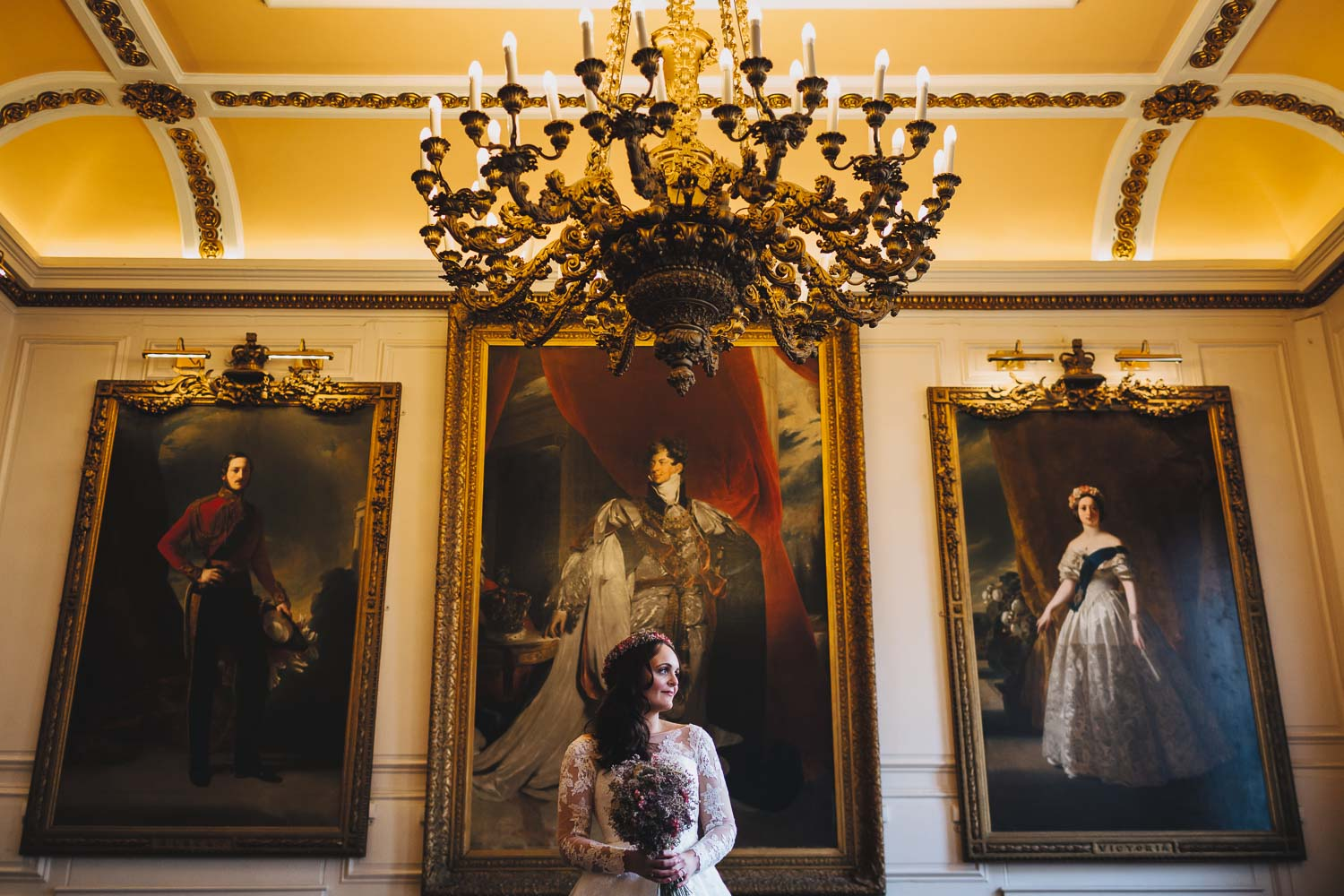 Bride standing in front of royal paintings in the Windsor Guildhall